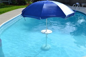 Table in swimming pool with umbrella